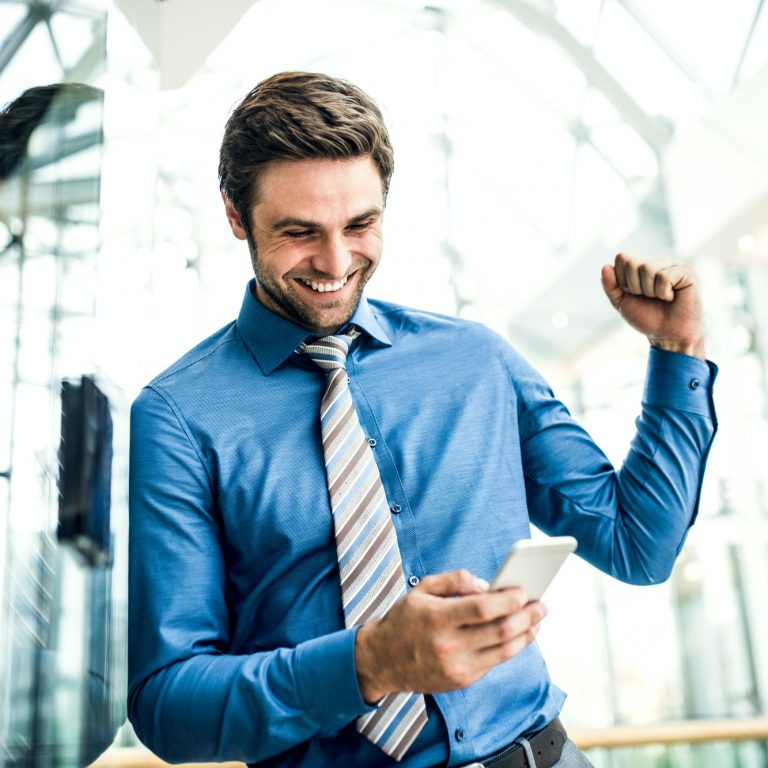A young businessman with smartphone, excited by good news.